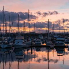 Boats docked in harbour at sunset