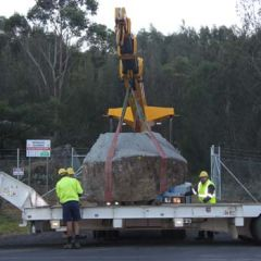 Moruya granite boulder being placed onto a trailer with a crane
