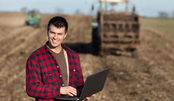 Farmer on laptop in field