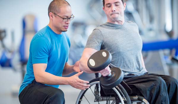 An instructor assisting a man in a wheelchair lifting a dumbbell