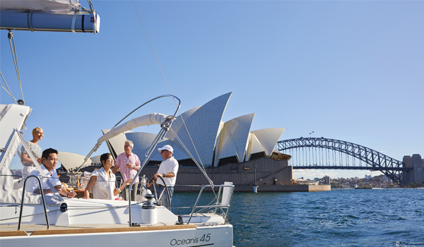 People in a yacht in the foreground, with the Sydney Opera House and Harbour Bridge in the background
