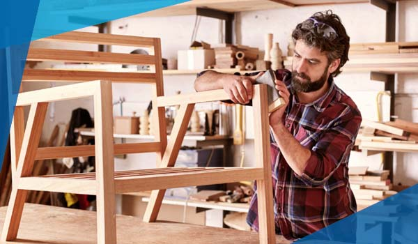 Image of a man making a chair out of wood