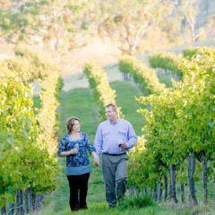 Two people walking through a vineyard