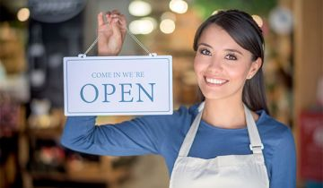 Woman holds a sign that reads: Open in front of a shop