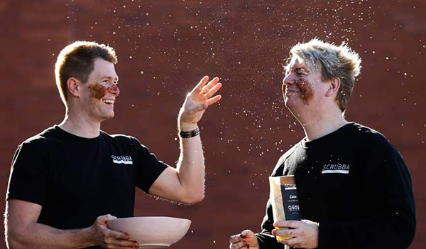 Two men with clay on their faces.