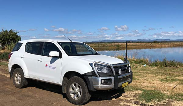 A department 4WD vehicle sits stationary close to the shore of a body of water.