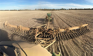 An NDF Ag-Design disc planter being pulled by a tractor.