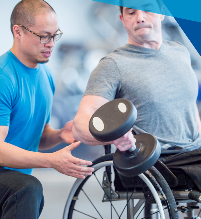 Man in wheelchair using dumbbell with therapist assisting
