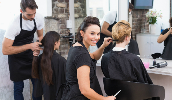 Hairdressers working on clients in salon