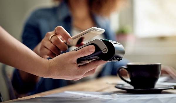 Customer paying for coffee through smart phone with EFTPOS machine