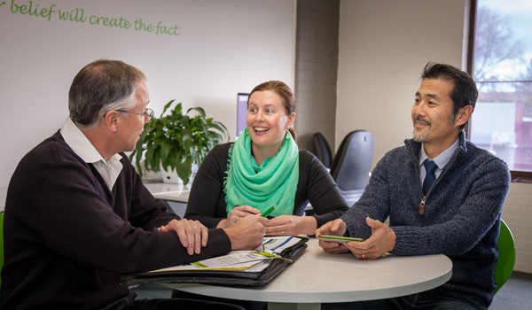 Three people around a table having a meeting