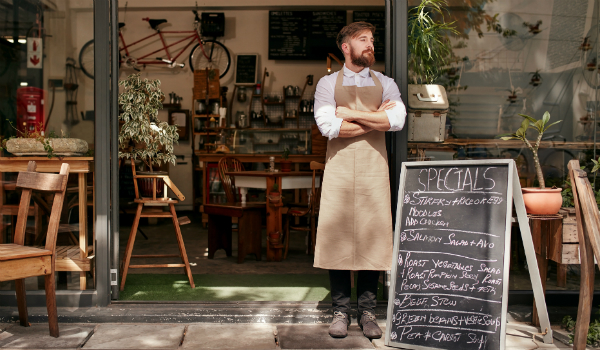 Waiter standing outside of cafe next to sandwich board