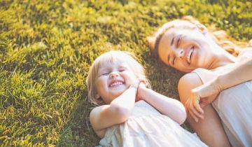 A photo of a child and her mother lying on green grass