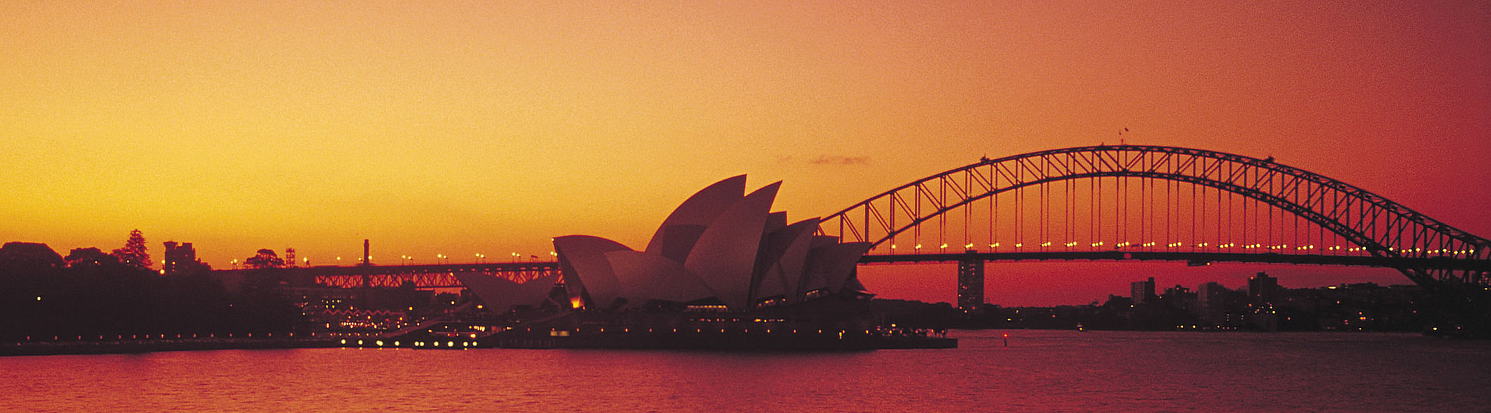A view of Sydney Harbour and the Opera House at dusk