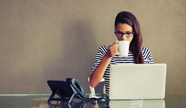 Woman drinking coffee looking at laptop