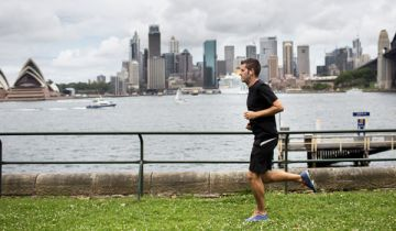 A runner in foreground with the Sydney Opera House and Harbour Bridge in background