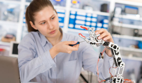 A woman with a screwdriver, fixing a robotic arm